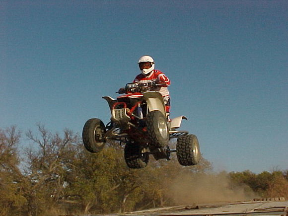 Me jumping a table top on our MX track right behind the house.