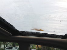 Looking up at the broken moon roof. Removal of the trim allows you to see two of the four screws that need removal with a T25 screwdriver. Clean out the broken glass from tracks and grease before dropping new glass unit into place. Loosely screw into place and adjust height of glass so that it is level with top of car, then tighten screws.